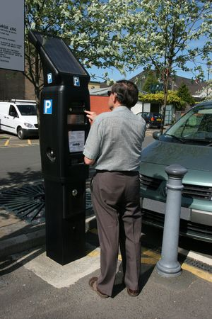 Elderly man buying a car parking ticket for a car park from a solar powered ticket machine. Banco de Imagens