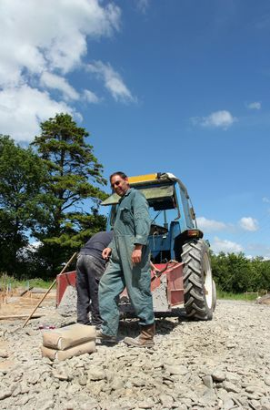Two men standing next to an old blue tractor with a red bucket to the rear filled with gravel. photo