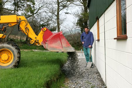 Gravel being tipped from a bucket on a telescopic loader onto a path under constrution and a man with a spade looking  on. photo