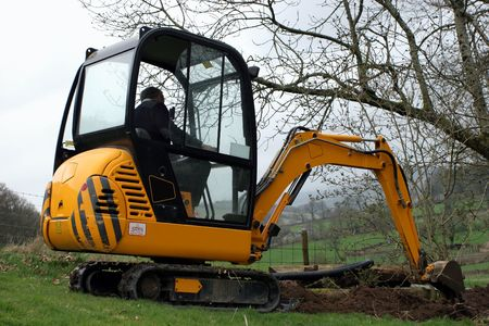 trench: Man in a mini digger digging a trench in a field.