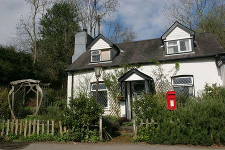Old quaint white cottage with leaded windows and a red post box to the foreground. photo