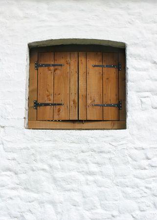 ironmongery: Granero ventana de madera fijado en una pared en una vieja piedra de cal de color blanco lavado granero.