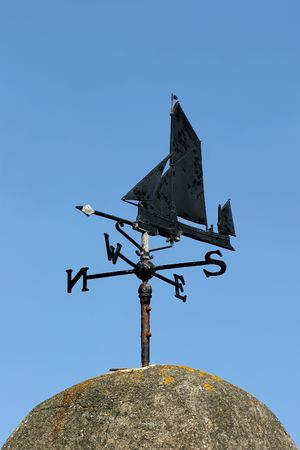 vane: Old black wrought iron weather vane of a ship design pointing west, set against a blue sky.