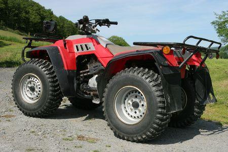 Four wheel drive red and black quad bike.