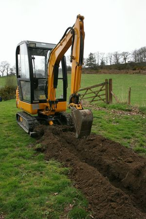 Mini digger standing in a field next to a newly dug trench. Stock Photo