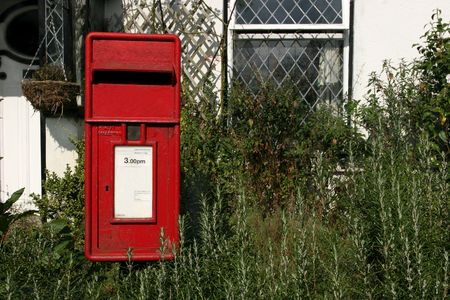 Old red post box surrounded by the fresh rosemary herb in front of an old white cottage. photo