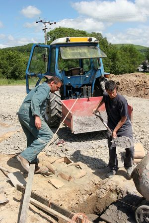 Two men mixing cement, with an old blue tractor with a red bucket filled with gravel to the rear. photo