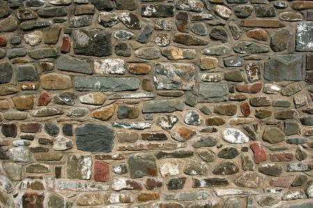 Old stone wall with varying sizes , shapes and colored stones. photo