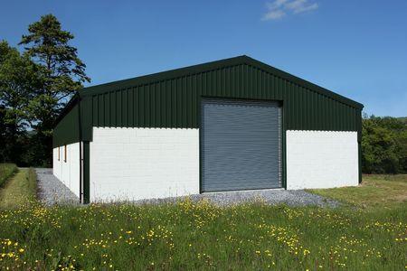Nouvellement construit grange de couleur crème murs en blocs de béton avec un toit de tôle verte volets roulants et portes, debout dans un champ de boutons, avec un ciel bleu et des arbres à l'arrière.  Banque d'images