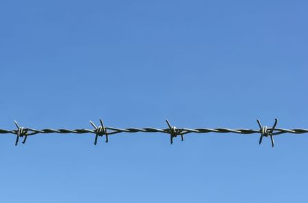 Barbed wire at a horizontal angle against a blue sky. Stock Photo - 455676