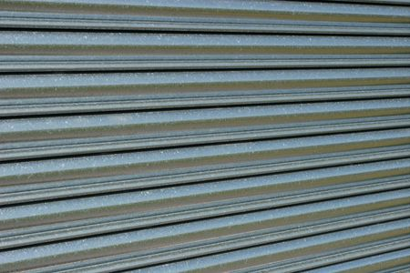 security shutters: Section of a steel roller shutter door on a diagonal slant.