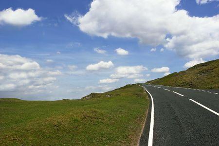 en mont�e: Mont�e en route d�serte campagne frise avec l'herbe de part et d'autre sur un ciel bleu avec des nuages. Situ� dans le parc national Brecon Beacons, au Pays de Galles, Royaume-Uni.