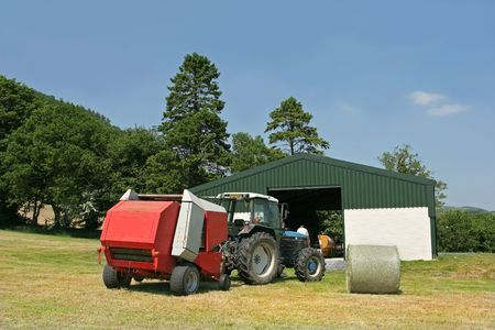 baler: Tractor and hay baler standing in a field in summer next to an agricultural barn with one circular hay bale in view. Set against a blue sky with trees to the rear. Stock Photo