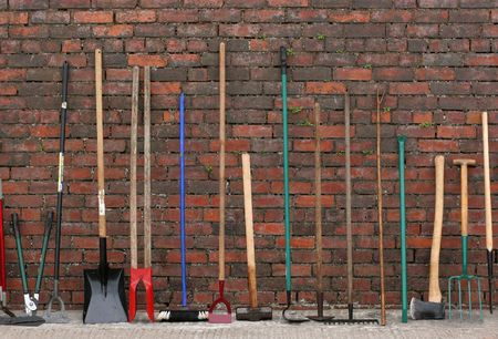 garden tool: Selection of hardware tools lined up vertically against a red brick wall.