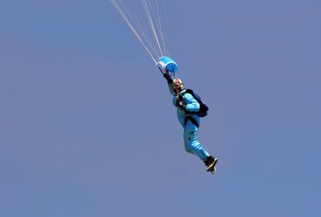 boiler suit: Male parachutist wearing a blue boiler suit, flying against a blue sky.