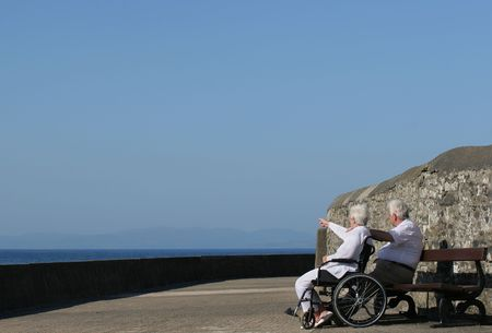 carers: Elderly woman in a wheelchair pointing at something in the distance and sitting next to an elderly man. Sea view and a blue sky in the background. Stock Photo