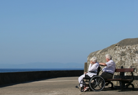 Elderly woman in a wheelchair with her hand on her head, seemingly depressed, and sitting next to an elderly man. Sea view and a blue sky in the background. Stock Photo