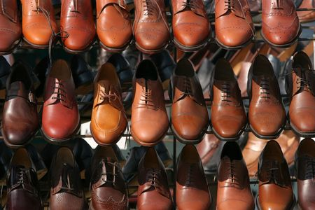 brogues: Lines of brown colored mens shoes on a stand. Stock Photo
