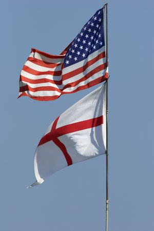 georges: American flag and the St Georges flag of England flying together against a blue sky.