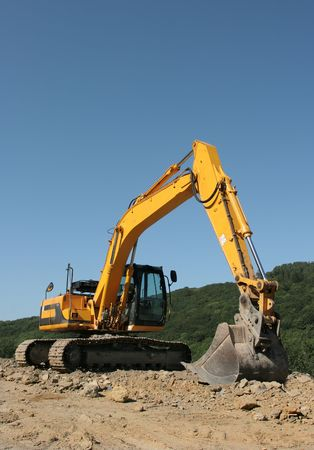 hardcore: Yellow digger standing idle on hardcore with trees and a blue sky to the rear. Stock Photo