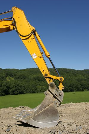 hardcore: Steel bucket of an earth excavator standing idle on hardcore with trees and a blue sky to the rear.
