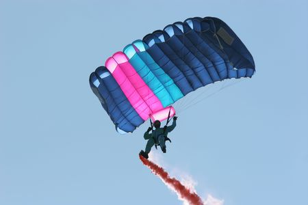 boiler suit: Parachutist in a blue boiler suit, with a pink and blue parachute, flying through the air with a red smoke trail coming from his right foot..
