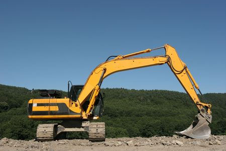hardcore: Large yellow digger standing idle on hardcore, with trees and a blue sky to the rear. Stock Photo