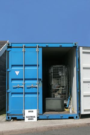 reusing: Blue metal recycling container for electrical goods, set against a blue sky.