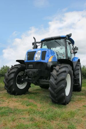 New blue and black four wheel drive tractor standing idle in a field. photo
