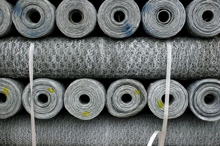 fencing wire: Stacked rolls of single strand metal chicken wire of different thicknesses, marked by yellow and blue paint.. Stock Photo
