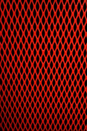 Red metal grill of diamond shaped mesh, against black. Stock Photo - 594789