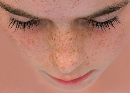 freckles: Face of a young girl with freckles with her eyes closed, as if in prayer. Stock Photo