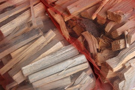 Cut firewood kindling in a net bag ready for selling. photo