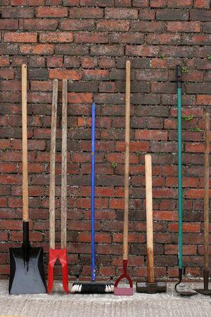 La sélection du matériel et des outils de jardinage debout ensemble contre un vieux mur de briques rouges.