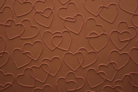 embossed: Double linked chocolate hearts embossed on brown paper.