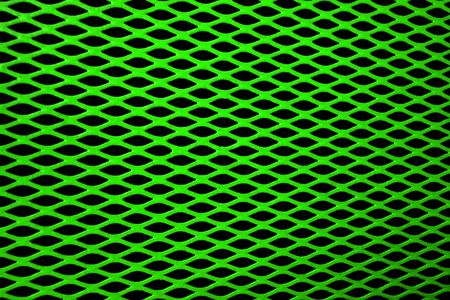 Green metal grill of diamond shaped mesh, against a black background. Stock Photo - 643194