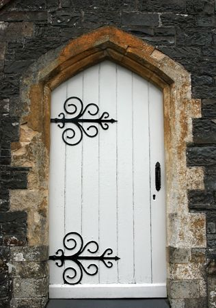 wrought: Old stone arched doorway with white wooden doors and black wrought iron accessories.