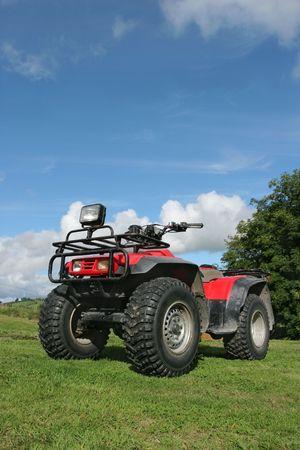 4 wheel: Cuatro ruedas motrices quad de pie en el c�sped de inactividad con un cielo azul y nubes de la parte trasera.