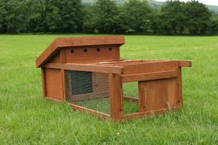 on the skids: Wooden chicken house with wire mesh run attached, standing on the grass in a field. Stock Photo