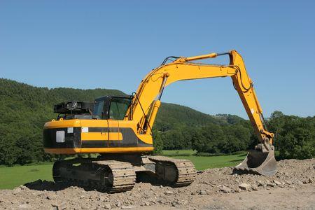 holgaz�n: Amarillo excavadora de inactividad permanente en un edificio obra de construcci�n rural con paisajes y un cielo azul en la parte posterior.  Foto de archivo