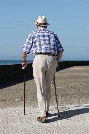 incapacitated: Rear view of an elderly man walking with walking sticks on a beach promenade.
