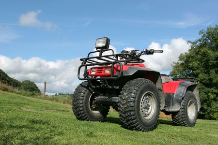 idle: Four wheel drive red and black quad bike standing idle on the grass, with trees and a blue sky with clouds to the rear.