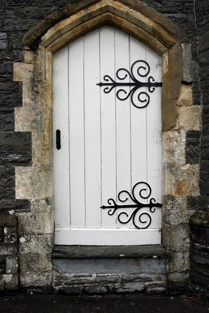 Old stone arched doorway with white wooden doors and black wrought iron accessories. Stock Photo - 695930