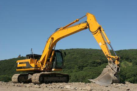 holgaz�n: Excavadora amarilla se cruza de brazos en un sitio de construcci�n de edificios y paisajes rurales con un cielo azul a la parte trasera. Foto de archivo