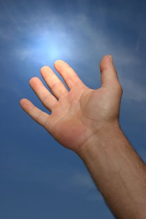 glowing skin: Hand of a man reaching to towards a blue sky with a light glow coming from his forefinger. Stock Photo
