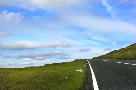 en mont�e: Trempez la route ascendante avec des bandes engazonn�es de chaque c�t� avec des nuages de cumulus dun ciel bleu et dalto r�gl�s dans les balises parc national, Pays de Gales, Royaume-Uni de Brecon.