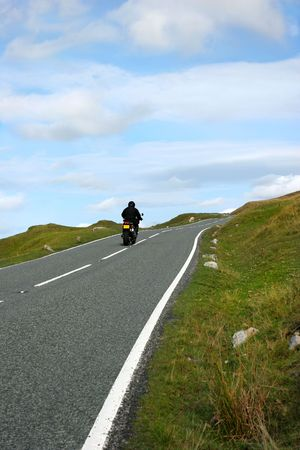 brecon beacons: Motorbike rider on an uphill mountain road in the Brecon Beacons National Park, Wales, United Kingdom.