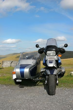 idle: Metallic blue and silver motorbike with side car standing idle on tarmac with rural countryside to the rear.