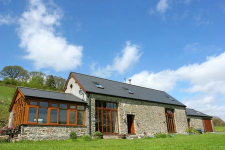 Newly restored residential stone barn with a slate roof in rural countryside against a blue sky with clouds. Stock Photo