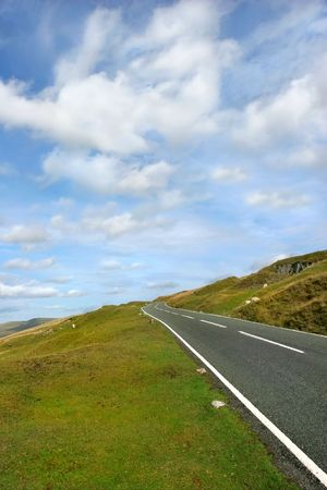either: Steep uphill road with grass verges on either side with a blue sky and alto cumulus clouds. set in the Brecon Beacons National Park, Wales, United Kingdom.